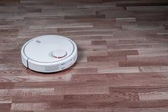 El aspirador robótico blanco corre en piso laminado Robot controlado por los controles por voz para la limpieza directa Elegante  imagenes de archivo