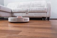 El aspirador robótico corre cerca del sofá en piso laminado Robot controlado por controles por voz de dirigir la limpieza Elegant fotos de archivo libres de regalías