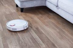 El aspirador robótico corre cerca del sofá en sitio en piso laminado Robot controlado por controles por voz de dirigir la limpiez imágenes de archivo libres de regalías