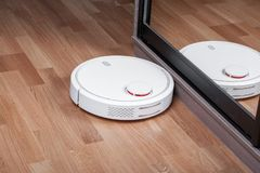 El aspirador robótico en piso laminado se refleja en el espejo del guardarropa, robótica casera elegante que la limpieza inalámbr foto de archivo libre de regalías