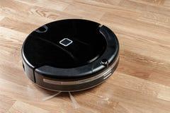 el aspirador robótico negro corre en piso laminado Economía doméstica elegante moderna de la tecnología de limpieza foto de archivo