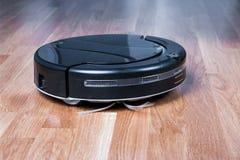 el aspirador robótico negro corre en piso laminado Robot controlado por los controles por voz para la limpieza directa Elegante m imagen de archivo