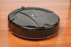 El aspirador robótico negro corre en el primer laminado del piso Robot controlado por los controles por voz para la limpieza dire fotografía de archivo