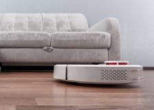 El aspirador rob?tico corre cerca del sof? en sitio en piso laminado Robot controlado por controles por voz de dirigir la limpiez fotos de archivo