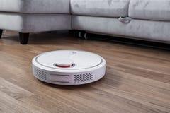 El aspirador rob?tico corre cerca del sof? en sitio en piso laminado Robot controlado por controles por voz de dirigir la limpiez imagen de archivo