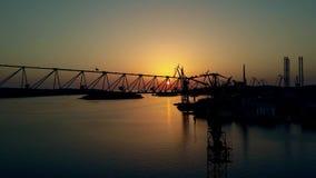 El astillero, grúa y el mar se abrigan en la puesta del sol metrajes