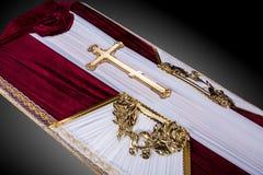 El ataúd cerrado cubierto con bordo y el paño blanco adornado con oro de la iglesia cruzan en fondo de lujo gris Primer Fotografía de archivo