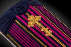 El ataúd cerrado cubierto con color rayó el paño adornado con la cruz del oro de la iglesia en fondo de lujo gris Primer Fotos de archivo