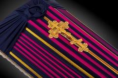El ataúd cerrado cubierto con color rayó el paño adornado con la cruz del oro de la iglesia en fondo de lujo gris Primer Imagenes de archivo