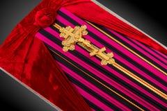 El ataúd cerrado cubierto con color rayó el paño adornado con la cruz del oro de la iglesia en fondo de lujo gris Primer Foto de archivo