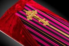 El ata?d cerrado cubierto con color ray? el pa?o adornado con la cruz del oro de la iglesia en fondo de lujo gris Primer fotos de archivo