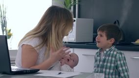 El ataque de nervios, madre con el bebé en brazos grita en su hijo que esté interfiriendo con el trabajo en casa almacen de video