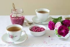 El atasco de los pétalos del Damasco subió, una taza de té verde y un florero de rosas en una tabla ligera Estilo rústico imagen de archivo libre de regalías
