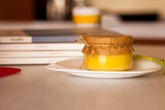 El atasco dulce del albaricoque en el tarro de cristal está en la tabla Foto de archivo libre de regalías