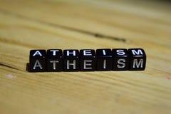 El ateísmo escrito en bloques de madera Conceptos de la inspiración y de la motivación fotos de archivo