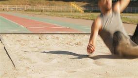 El athlet masculino hace un salto de longitud en el estadio almacen de video