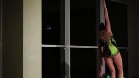 El atleta atractivo lindo delgado de la muchacha en traje de baño colorido brillante realiza elementos de la gimnasia rítmica con