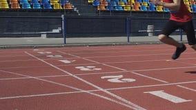 El atleta caucásico en la respiración pasada cruza la meta y al ganador que se convierte de la raza metrajes