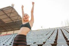 El atleta cauc?sico hermoso de la muchacha aument? sus manos para arriba como ganador imagenes de archivo