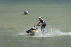 El atleta de la muchacha diseca audazmente ondas del mar en aquabike imagenes de archivo