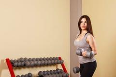 El atleta de la muchacha entrena al bíceps con pesas de gimnasia Imagenes de archivo