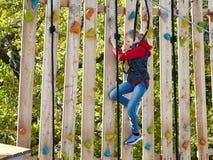 El atleta de la muchacha funciona con una carrera de obstáculos en parque que sube Foto de archivo