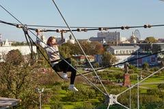 El atleta de la muchacha funciona con una carrera de obstáculos en parque que sube Fotografía de archivo libre de regalías