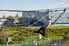 El atleta de la muchacha funciona con una carrera de obstáculos en parque que sube Imágenes de archivo libres de regalías