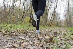 El atleta de la muchacha, mujer que corre en zapatillas de deporte en la pista en Imagenes de archivo