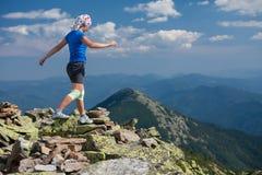 El atleta de la mujer está saltando sobre piedras imagen de archivo libre de regalías