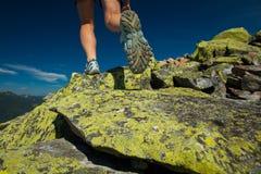 El atleta de la mujer está saltando sobre piedras en montañas fotos de archivo