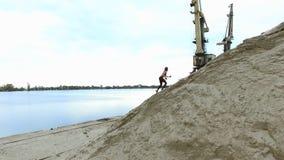 El atleta de la mujer joven sube una montaña arenosa En el fondo se puede ver el río, grúas del cargo, puerto del cargo, amanecer metrajes