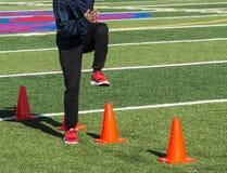 El atleta de pista de la High School secundaria que hace velocidad perfora sobre conos Fotografía de archivo
