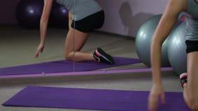 El atleta de sexo femenino activo acaba entrenamiento, se levanta de la estera y deja el gimnasio de la aptitud almacen de video