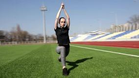 El atleta de sexo femenino activo atractivo joven apto que hace posiciones en cuclillas calienta el estadio grande exterior de el almacen de video
