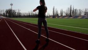 El atleta de sexo femenino activo atractivo joven apto que hace posiciones en cuclillas calienta el estadio grande exterior de el almacen de metraje de vídeo