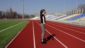 El atleta de sexo femenino activo del ajuste atractivo joven que hace posiciones en cuclillas calienta el estadio grande exterior almacen de metraje de vídeo