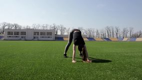 El atleta de sexo femenino del ajuste atractivo joven activo que hace posiciones en cuclillas calienta el estadio grande exterior almacen de video