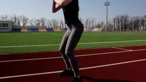 El atleta de sexo femenino del ajuste atractivo joven activo que hace posiciones en cuclillas calienta el estadio grande exterior metrajes