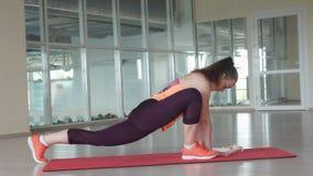 El atleta de sexo femenino joven hace ejercicio que estira difícil en la estera del gimnasio mientras que entrena en el gimnasio foto de archivo libre de regalías