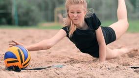 El atleta de sexo femenino joven se zambulle en la arena y ahorra un punto durante partido del voleibol de playa La muchacha cauc metrajes