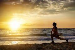 El atleta de sexo femenino realiza sus estiramientos en una playa imagen de archivo