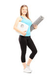 El atleta de sexo femenino sonriente que lleva a cabo un peso escala y estera Foto de archivo libre de regalías