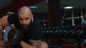 El atleta de sexo masculino centrado en pesa de gimnasia se encrespa, construyendo el bíceps, entrenamiento activo en gimnasio metrajes