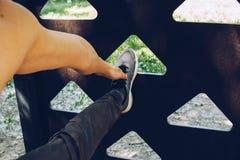 El atleta de sexo masculino en la situación de funcionamiento de los zapatos de los deportes estira su pierna en el campo de depo imágenes de archivo libres de regalías