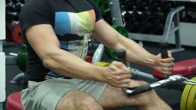 El atleta de sexo masculino entrena en el simulador en el gimnasio Cámara lenta metrajes
