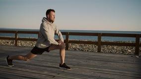 El atleta de sexo masculino está haciendo estocadas en la plataforma de madera en orilla de mar almacen de video