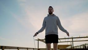 El atleta de sexo masculino está saltando al aire libre en tiempo de mañana, usando cuerda que salta almacen de video