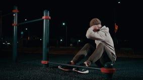El atleta de sexo masculino está trabajando con los músculos del cuerpo superior en noche en el parque, torso de la elevación metrajes
