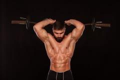 El atleta de sexo masculino muscular está entrenando levantando el barbell Fotografía de archivo